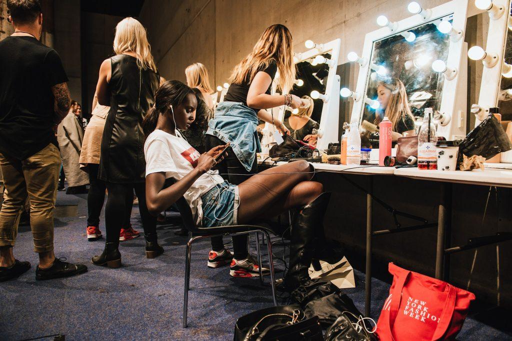 en esta foto se ve a unas chicas maquillándose y peinándose
